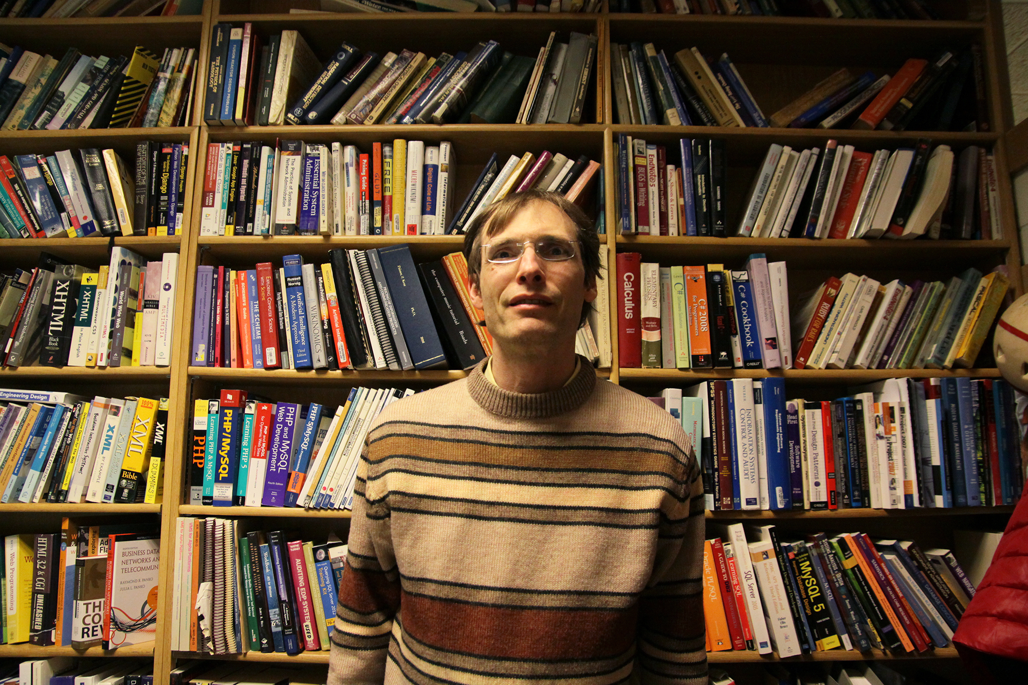 Kent Palmer stands in front of a large bookshelf full of books