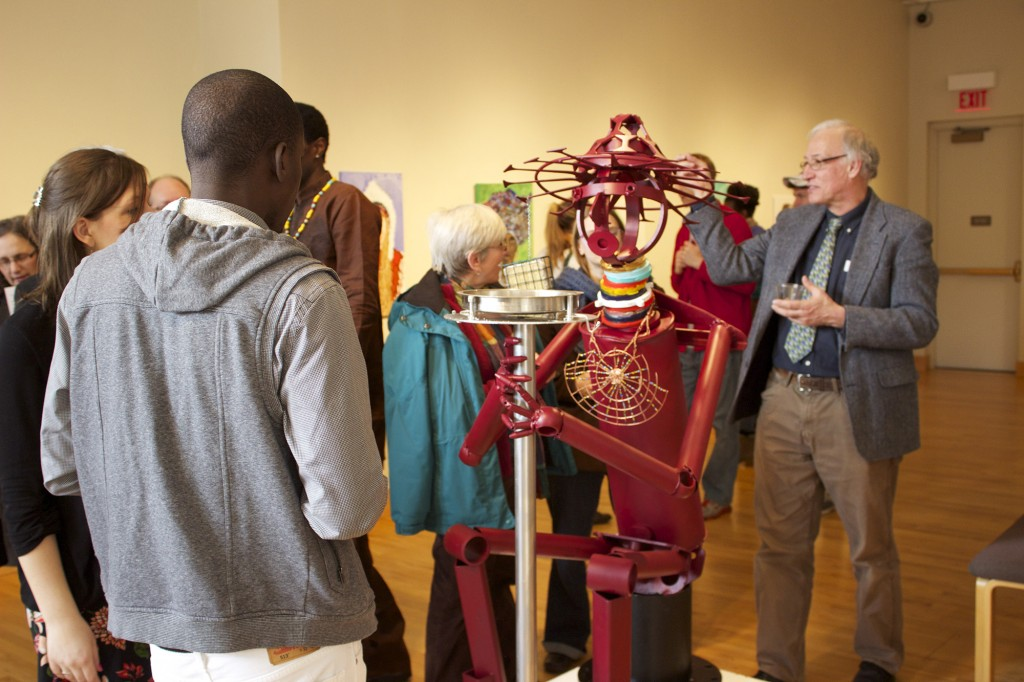 "Reception attendees gather around Sunday Mahaja's sculpture entitled ""Housa Man."""
