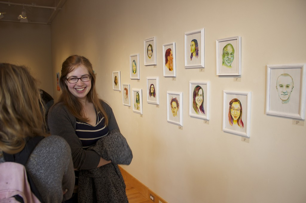 Kate Yoder, a junior, stands in front of portraits by Liz Reese.