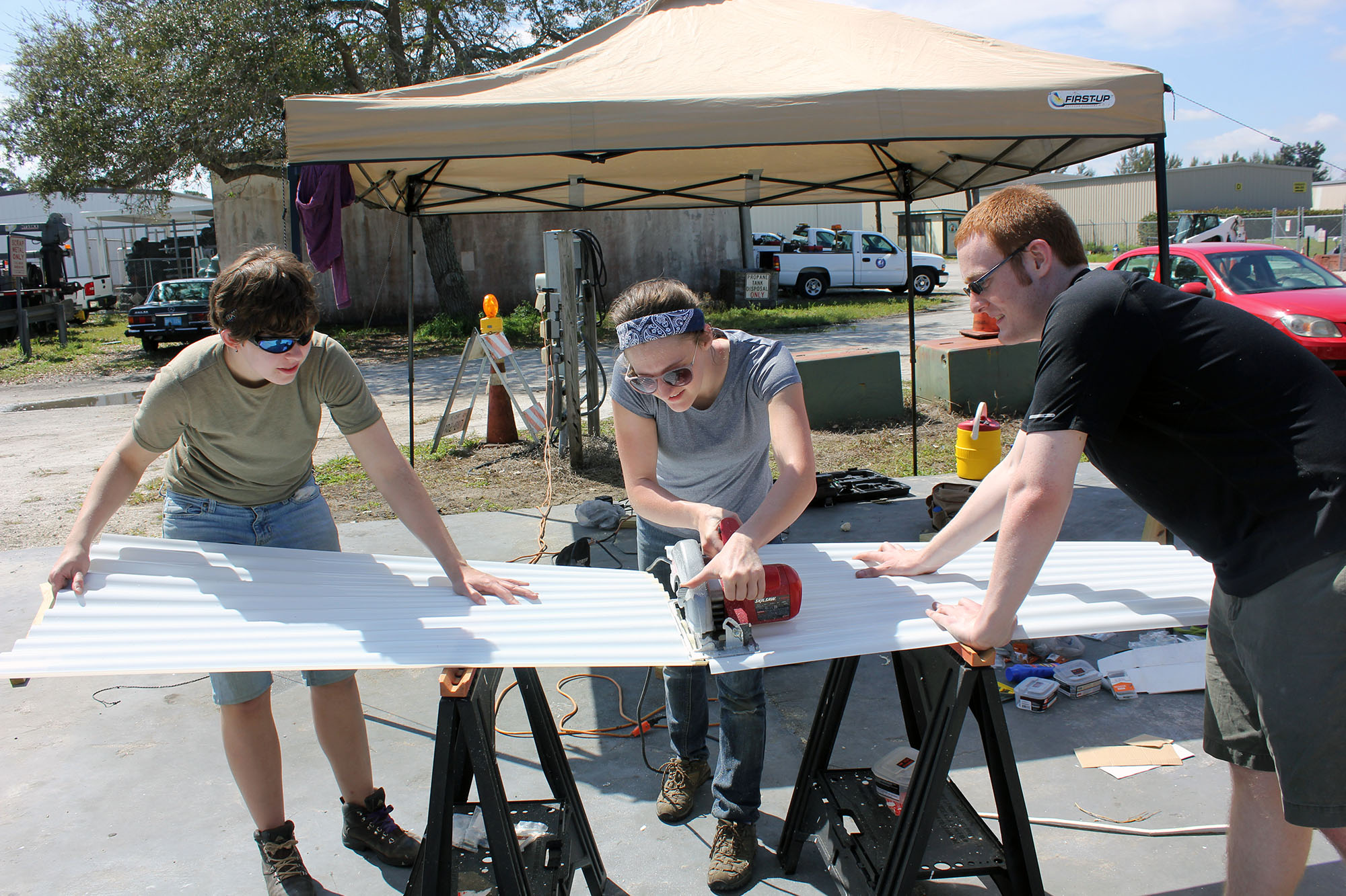 Natalie Weisenbeck and two other students cut boards outdoors in Florida