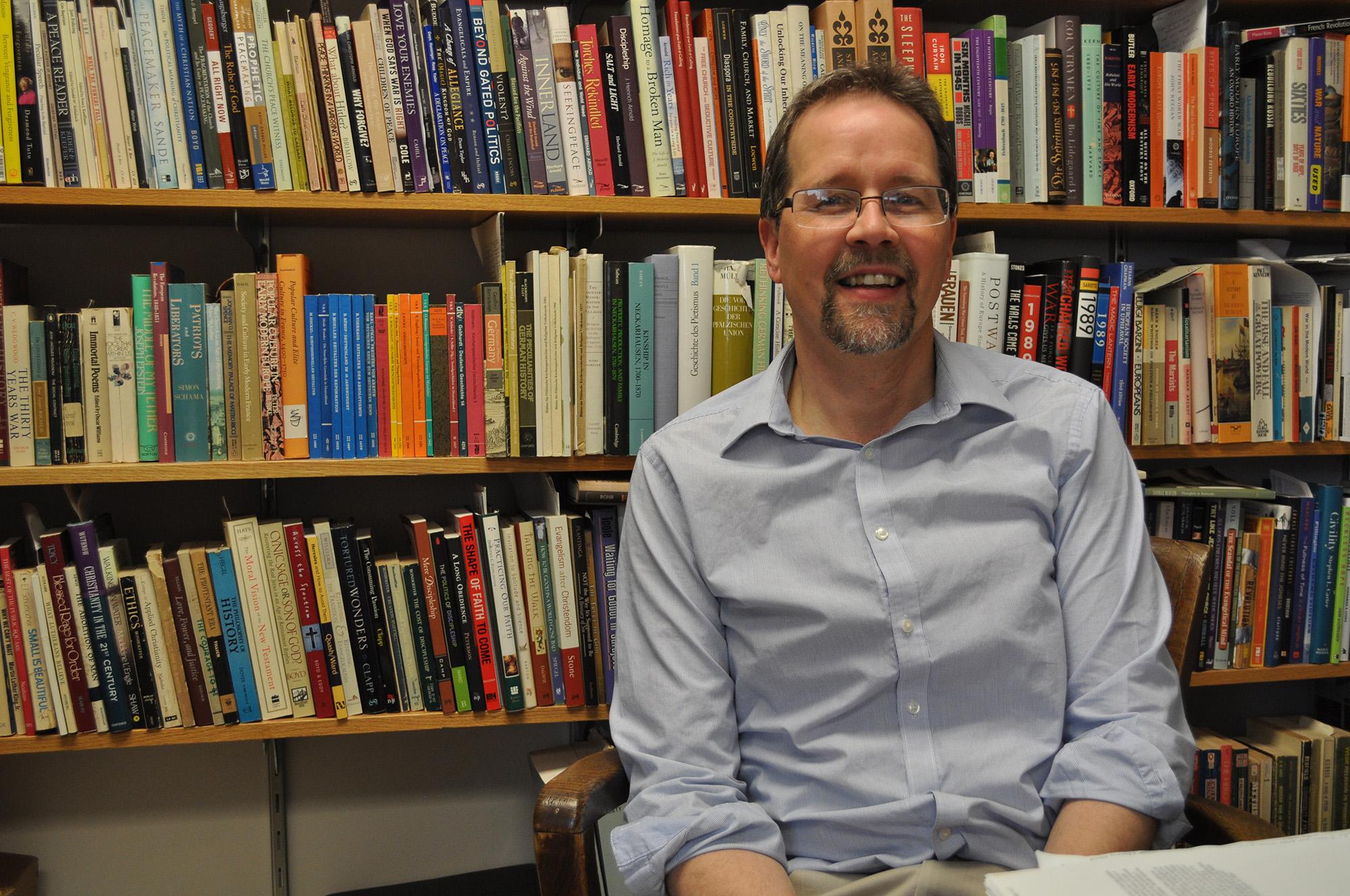 John Roth smiles in front of a bookshelf full of books
