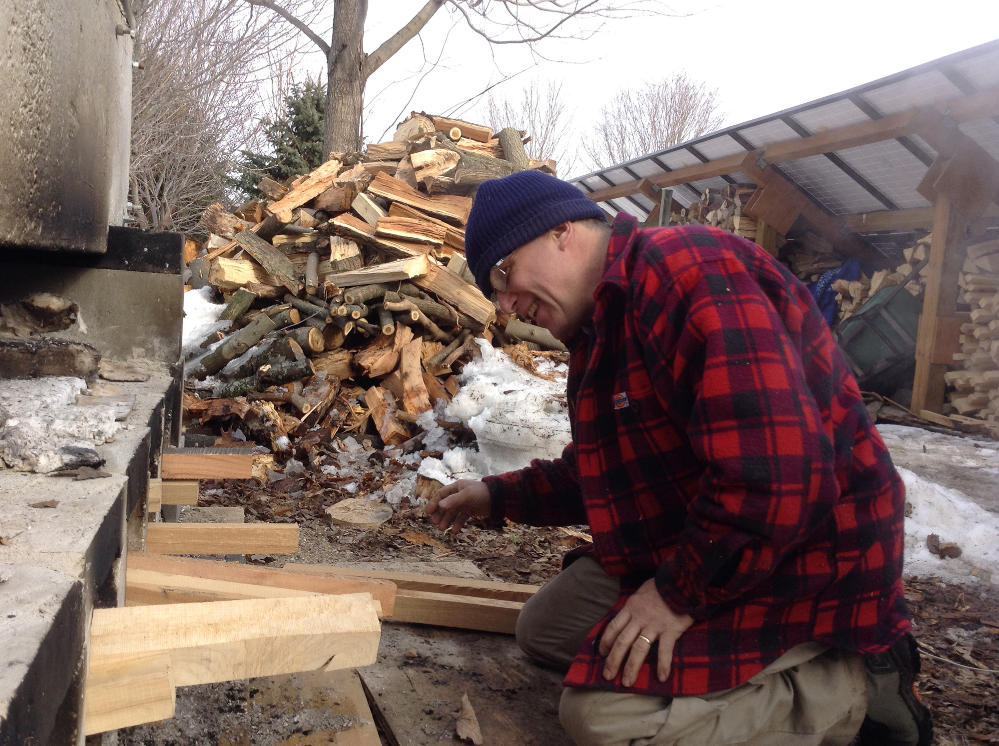 Wearing a red flannel and a beanie, Steve Shantz inspects his large firewood pile