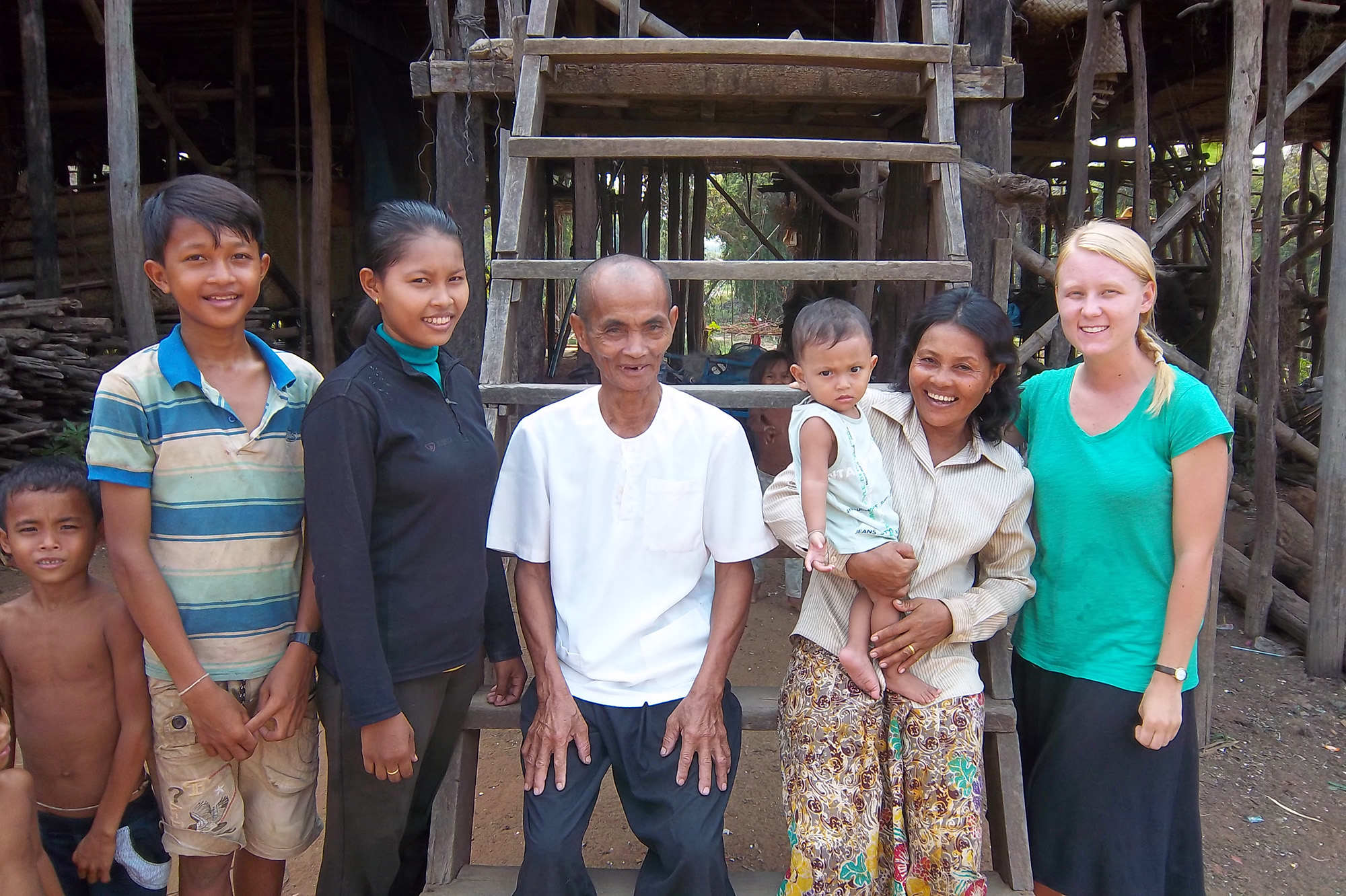 Audrey Thill smiles for the camera with the six members of her Cambodian host family