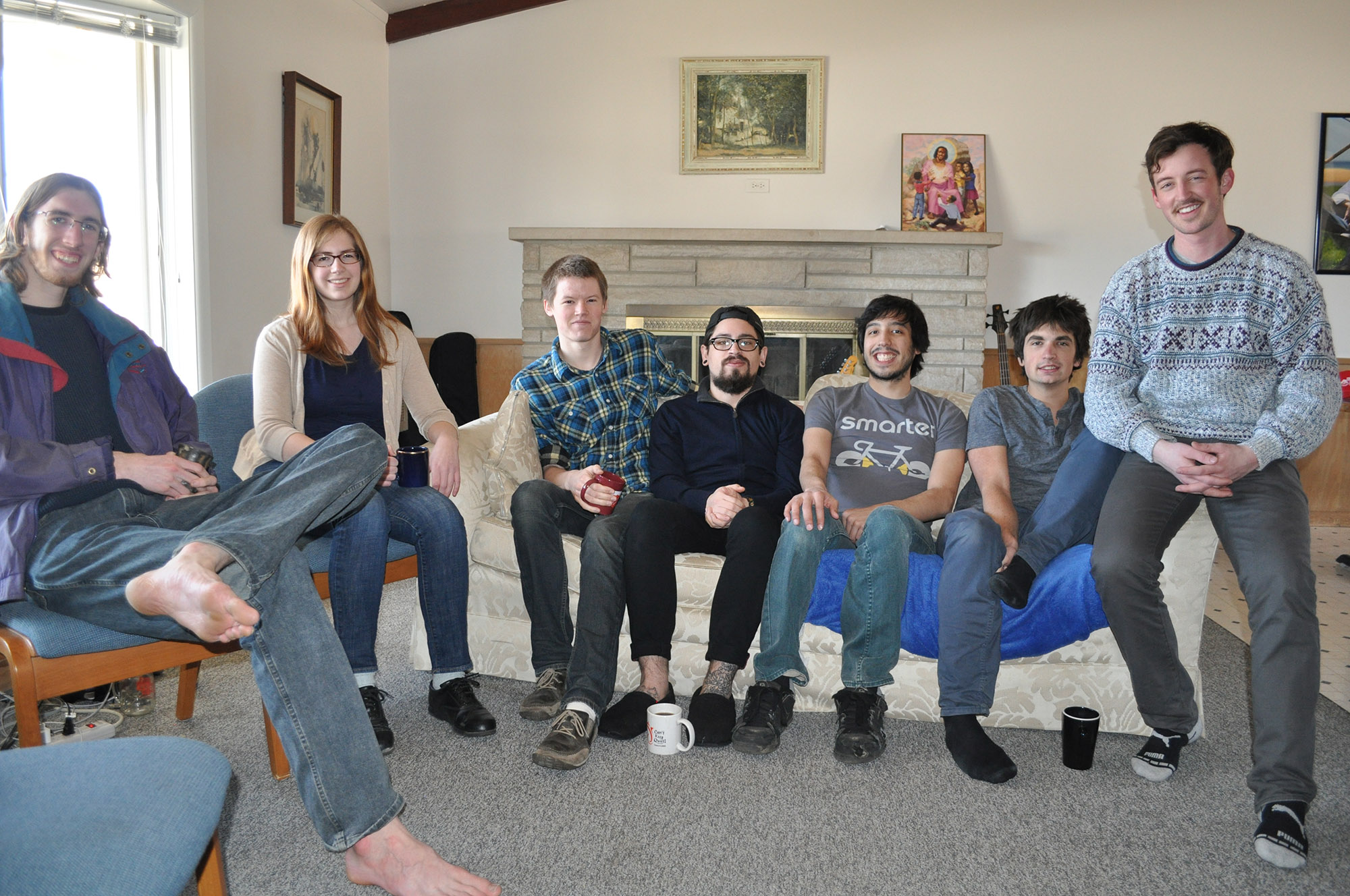 7 members of the Goshen Skeptics sit around a small room and smile for the camera