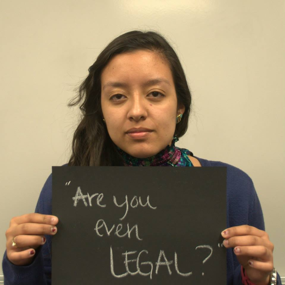 """Student with microaggression sign that says """"Are you even legal?"""""""