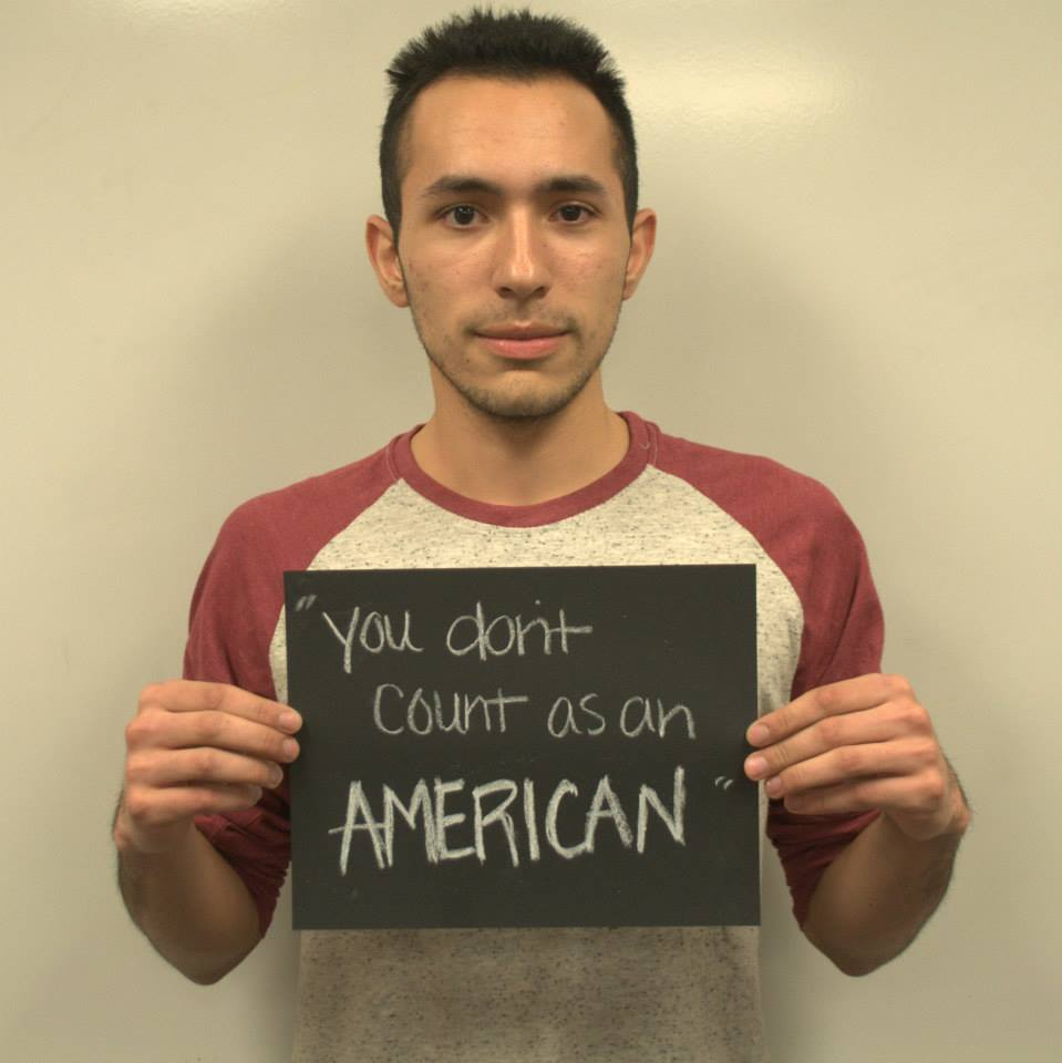 """Student with microaggression sign that says """"you don't count as an American"""""""
