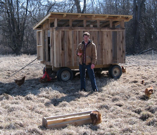 A student stands in front of a large, wooden chicken coop in a field. The coop is mobile due to the built-in wheels.