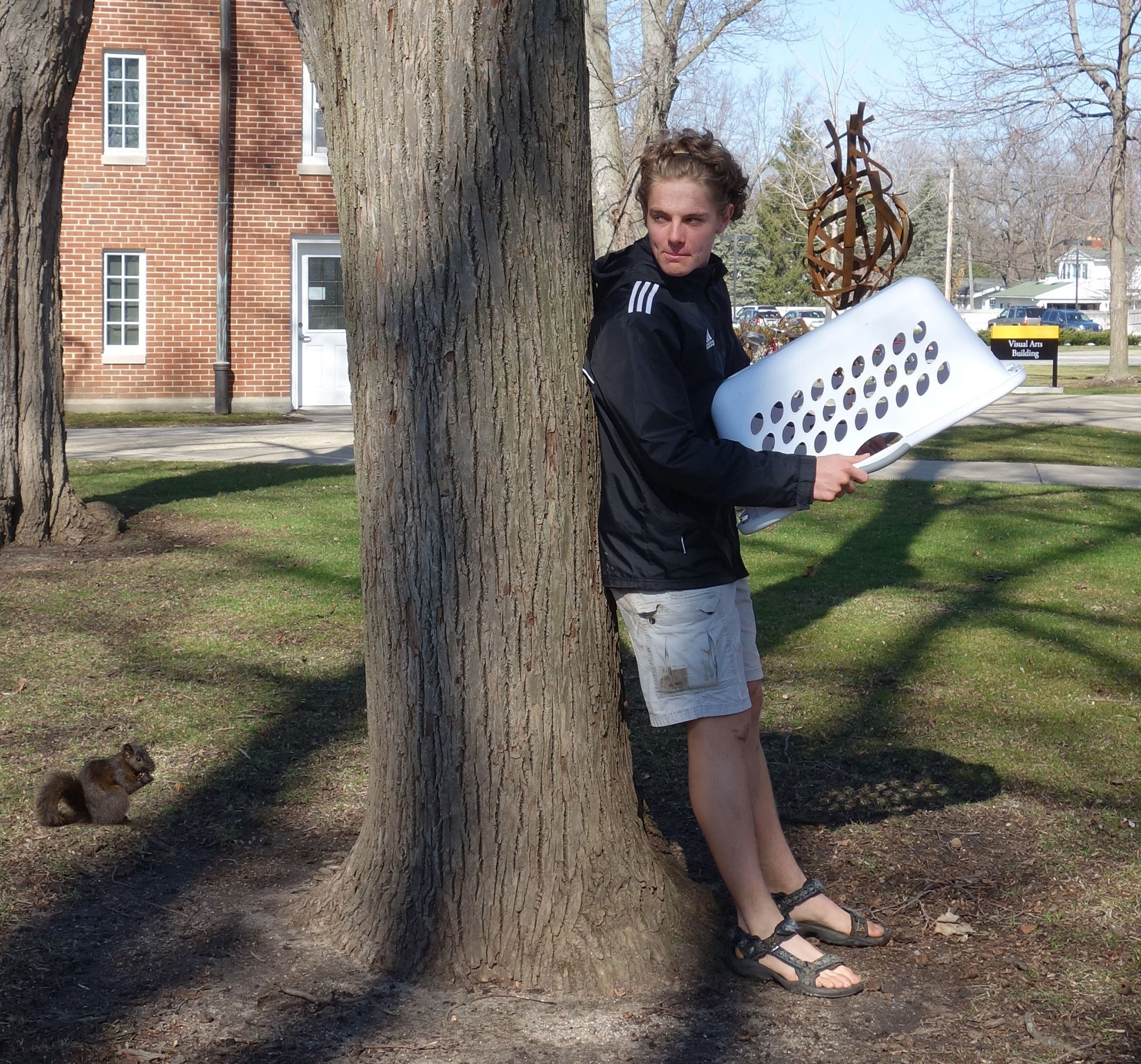 David Jantz hides behind a tree with a laundry basket, planning to jump out and capture the squirrel behind the tree