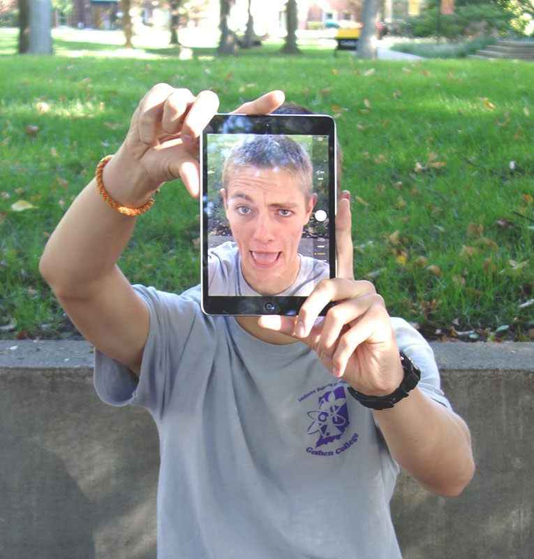 David Jantz holds an iPad's camera in front of his face, showing his face through the iPad screen