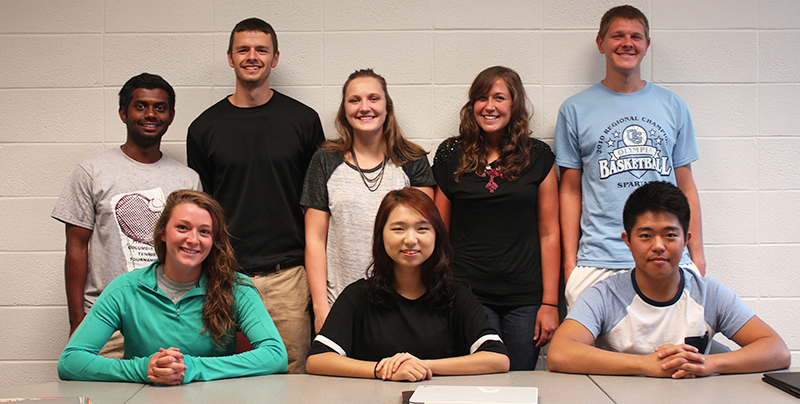 Eight members of the Java Junction management class pose for a picture; three of the students sit at a desk, while the other five stand behind them in a line.