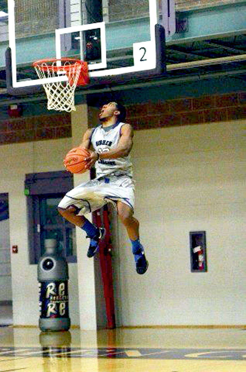 Wearing a Goshen College jersey, Jerron Jamerson holds a basketball and jumps toward the hoop in the RFC gym