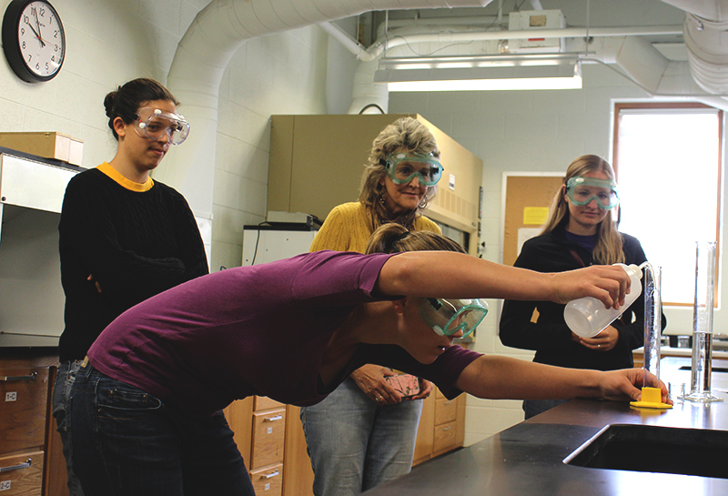 Kara Hostetter, Ellie Schertz and two other students wear safety goggles while completing an experiment in a lab in the science building