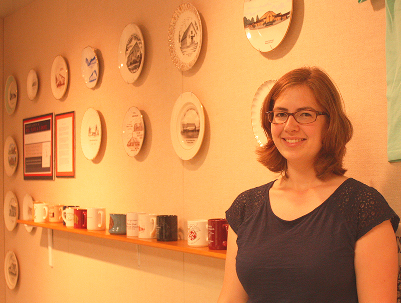 Kate Yoder with a wall of ceramics