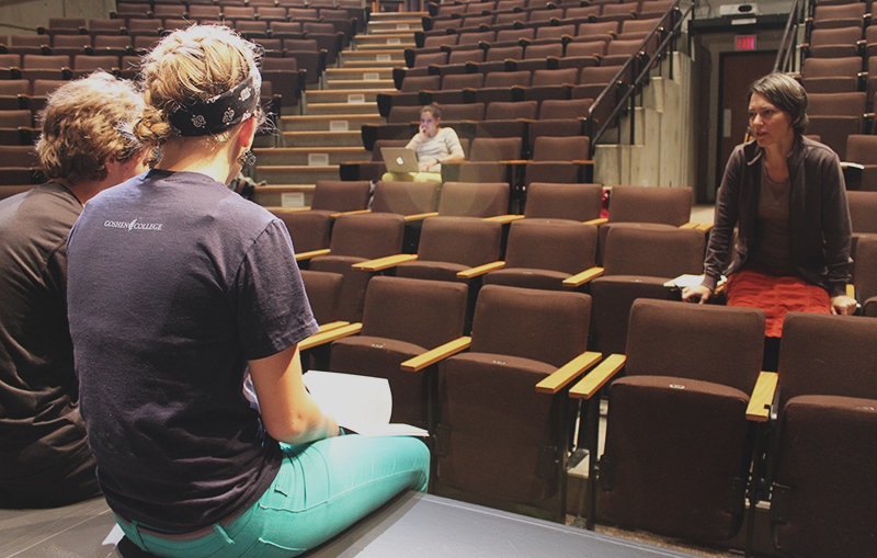 Michelle Milne stands in the Umble Center audience and directs two students sitting onstage