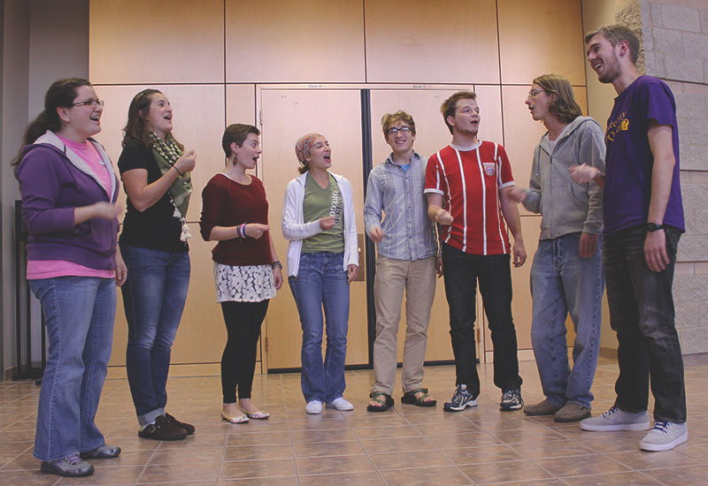 8 members of Parables stand in a semi-circle and perform on the Sauder Concert Hall stage