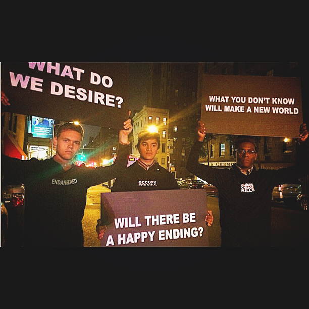 """Three students hold up signs during the climate march. The first sign reads """"What do we desire?"""", the second sign reads """"will there be a happy ending?"""", and the third sign reads """"what you don't know will make a new world"""""""