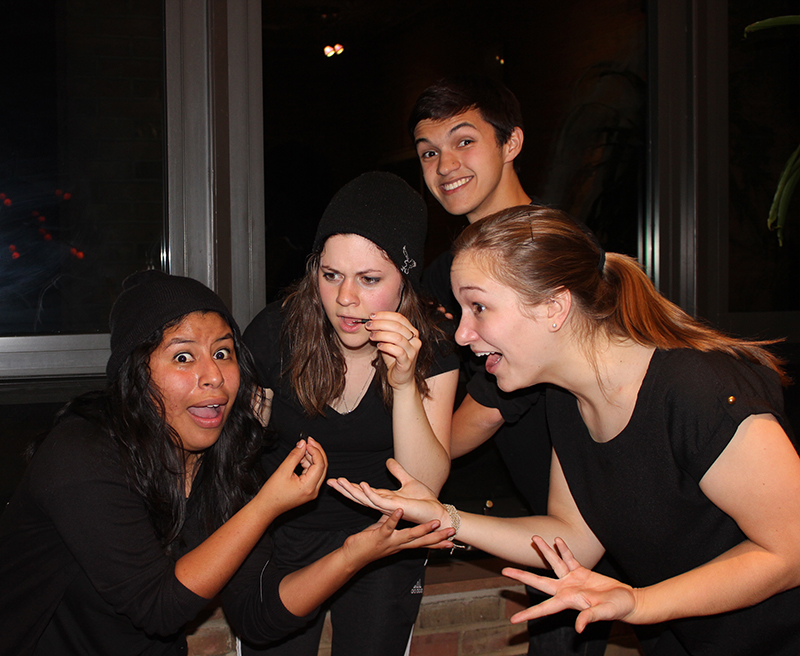 Four students wearing black make various funny faces for the camera