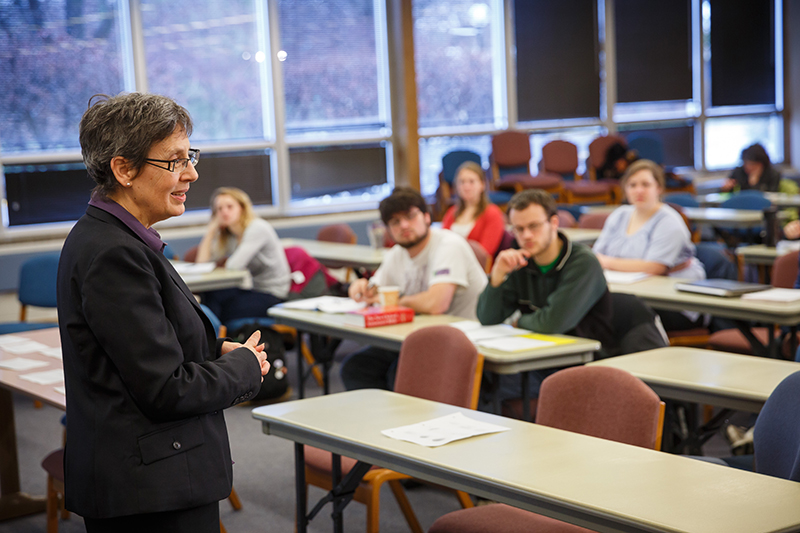 Jo-Ann Bryant lectures in classroom Newcomer 17. Five students are sitting at desks.