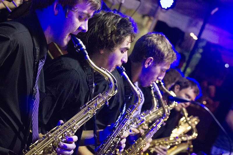 Four members of Lavender Jazz play saxophone and other brass instruments at a concert venue.