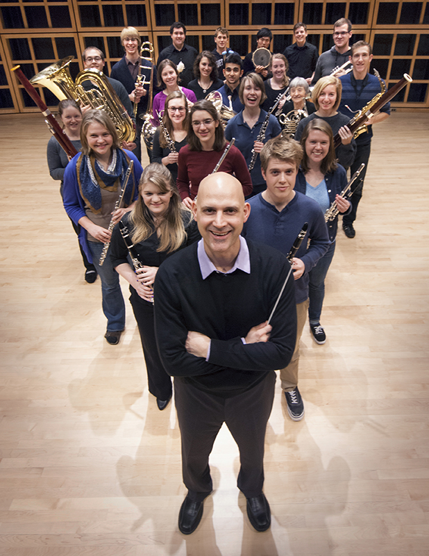 Christopher Fashun smiles up at the camera as members of the All-Campus Band form a triangle behind him in Sauder Concert Hall. The musicians are all holding their instruments