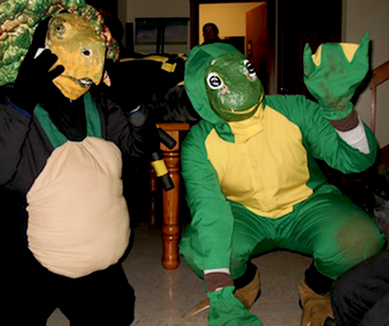 Two students dressed as animals pose for the camera. One student is dressed as a green and yellow frog, while the other is dressed as a turtle