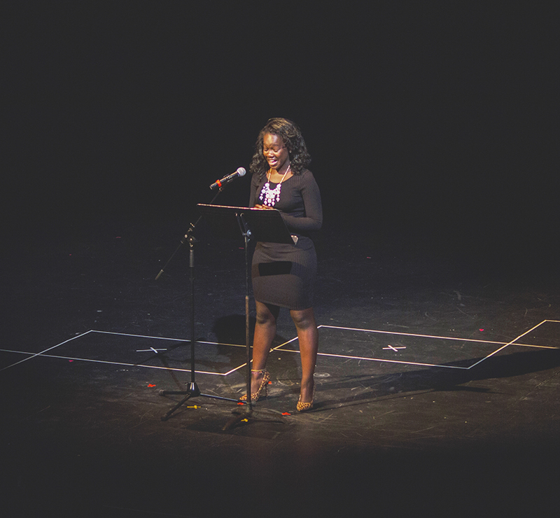 Annie Agutu speaks into a microphone in Umble Center, illuminated by a spotlight.