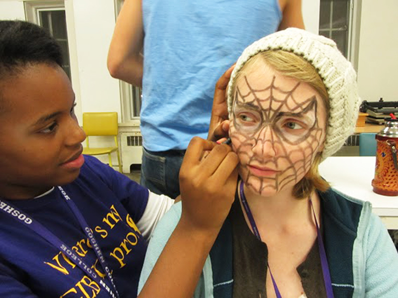 A member of art club draws a spiderweb on a child's face using face paint
