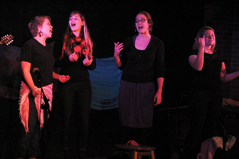 Four performers sing in a dimly lit Newcomer 19 for Chocolate House