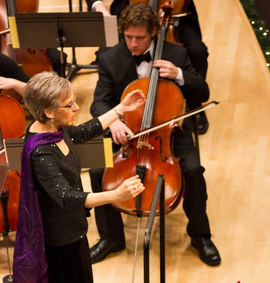 Overhead shot of Dr. Debra Brubaker conducting during a concert in Sauder Concert Hall. To her left are two cello players