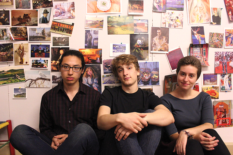 Ethan Setiawan, Andrew Pauls, and Sadie Gustafson-Zook lean against a wall covered in photos and drawings