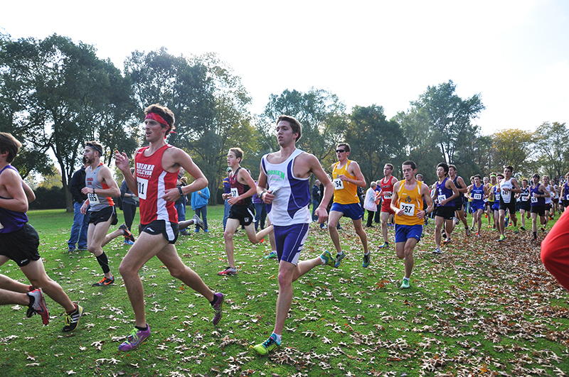 Many cross country runners pass by the camera at an outdoor meet. One of the runners wears a Goshen College jersey