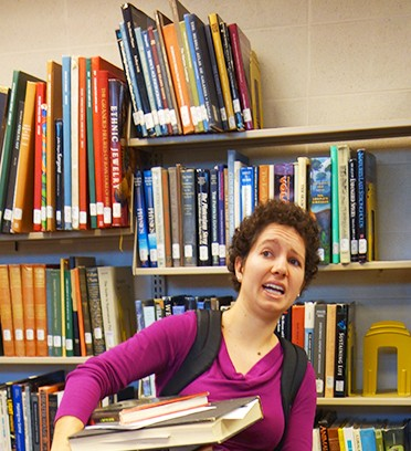 Maria Jantz carries a stack of books through the Good Library