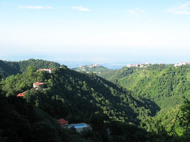 Aerial image of a beautiful, green mountain range in India. The ocean is visible in the distance, and the mountain range is dotted with red and brown buildings
