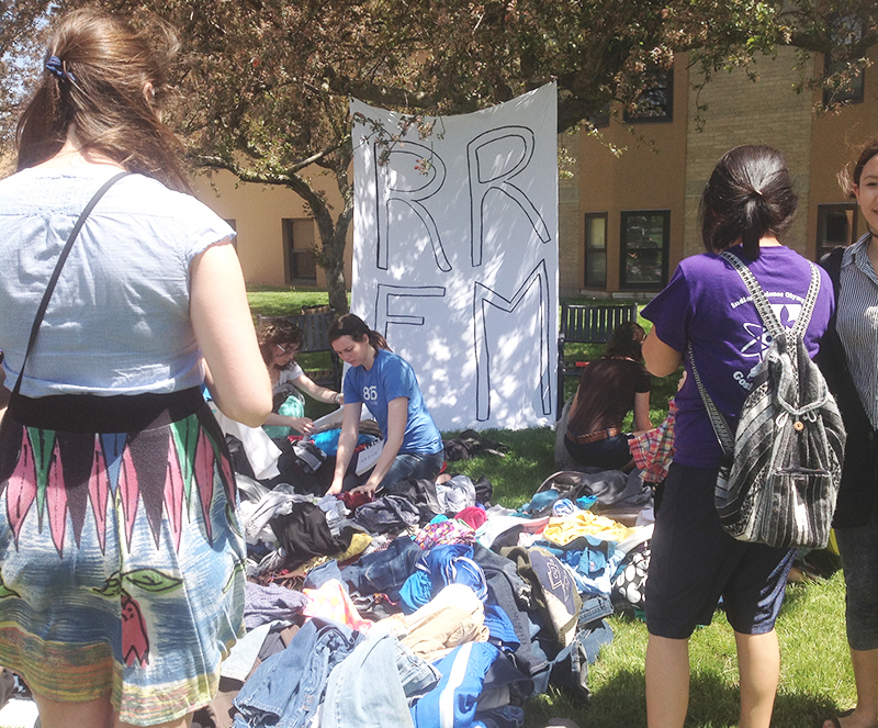 """Students look through piles of clothes on the KMY lawn. A fabric sign reading """"RRFM"""" hangs from a tree"""