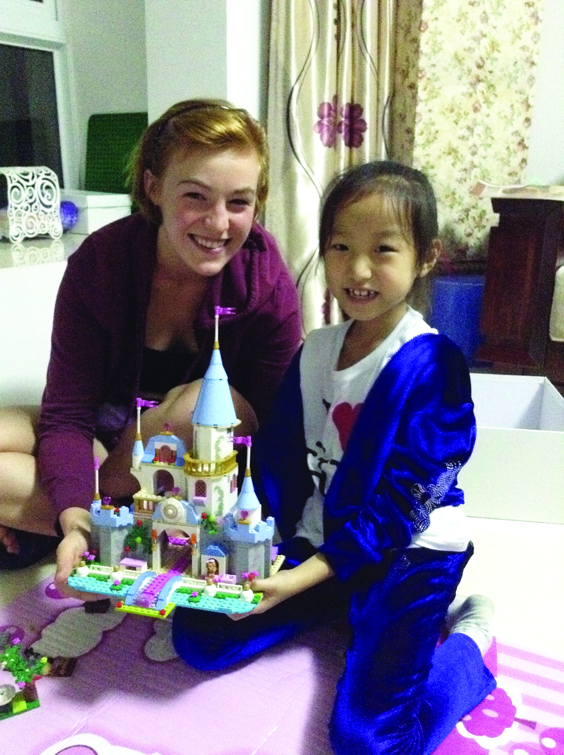Ellen Conrad and her Chinese host sister hold a toy castle and smile for the camera