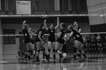 Volleyball scholar athletes Sam Heberling, senior, Natalie Hubby, junior, and Kelsey Smith, junior, celebrate a point with the team