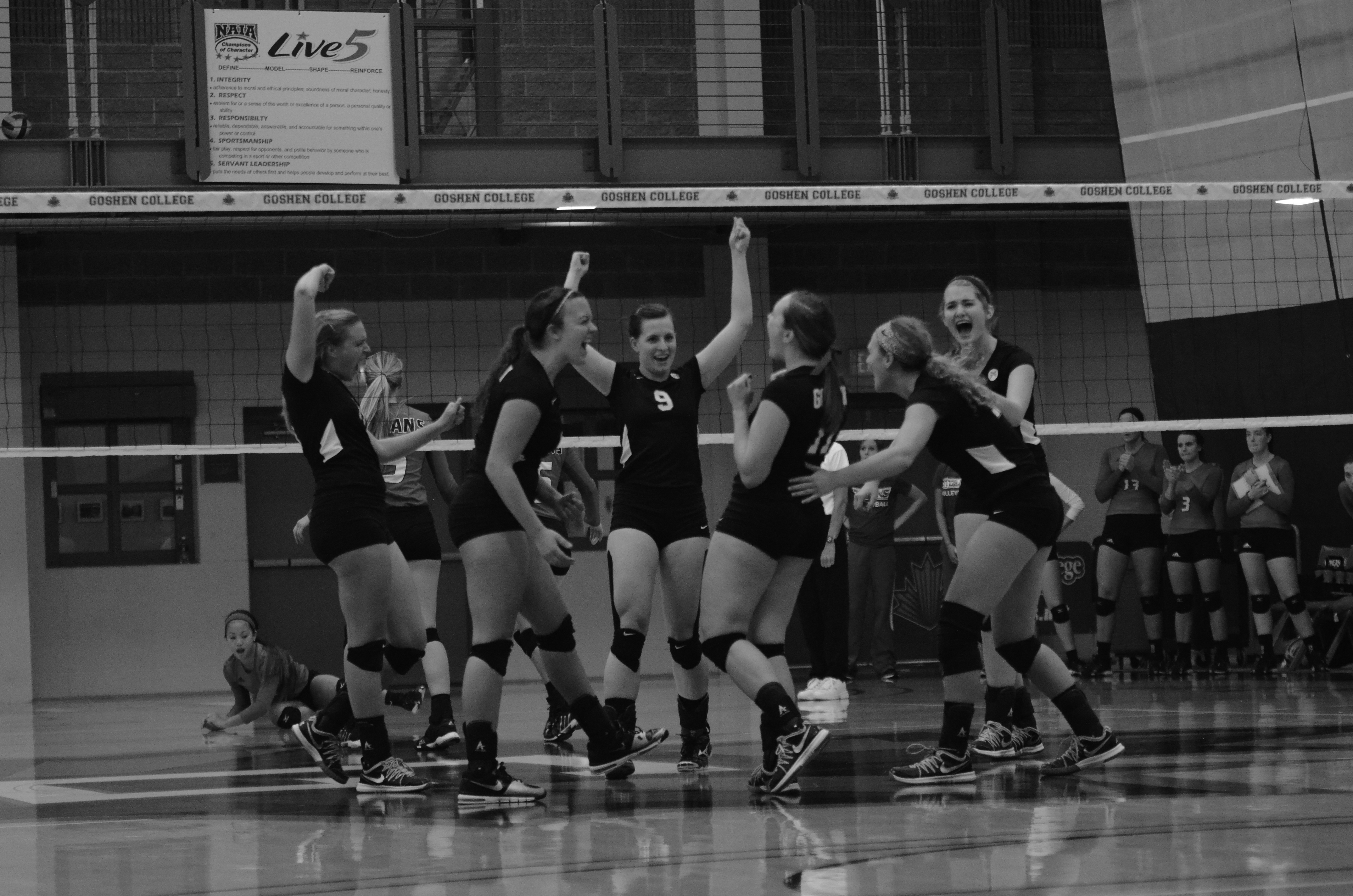 Black and white image of Goshen volleyball players celebrating a point during a game