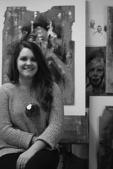 Jama Yoder, a senior, poses with her art in the visual art building.