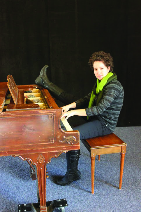 Maria Jantz plays the piano while simultaneously resting her right foot on top of it