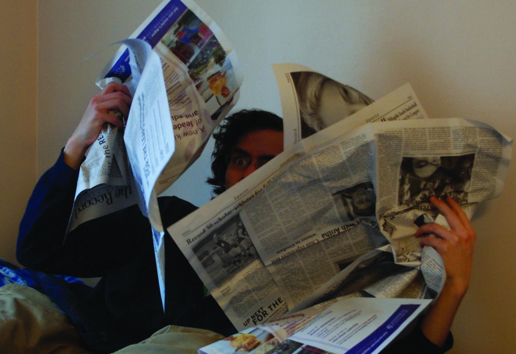 Reuben Ng hidden behind several Record newspapers