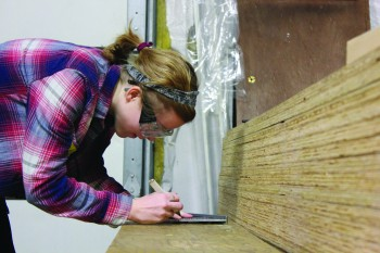 Kayla Gray, sophomore, measures out a line to make a cut while working for Habitat for Humanity.