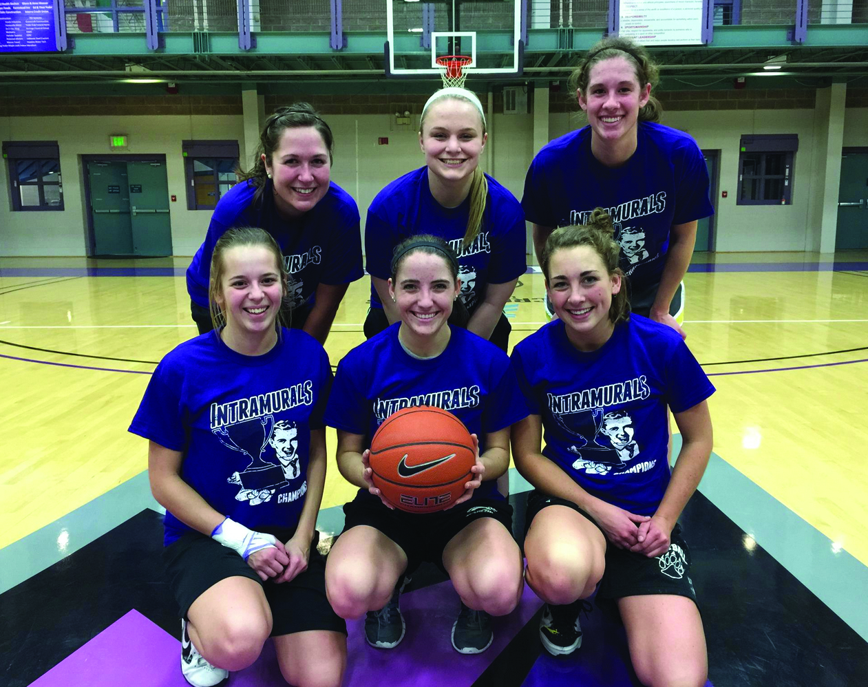 """The six players of the intramural basketball team """"Short Stack"""" pose for a picture in the RFC. They are wearing Goshen Intramural T-shirts, and one of them is holding a basketball"""
