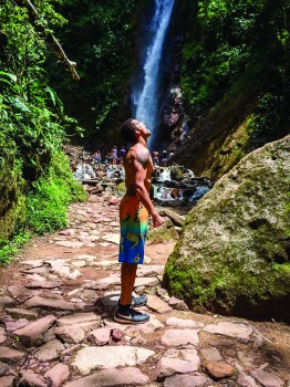 Trevor Emory, junior exercise science major, stands in front of a waterfall in San Ramon, Peru