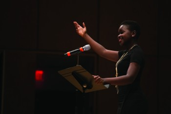 Annie Agutu, first-year, raises her hand to the audience during her spring Kick Off performance