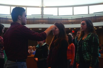 Junior Paul Zehr anoints first-year Jill Steinmetz in observance of Ash Wednesday