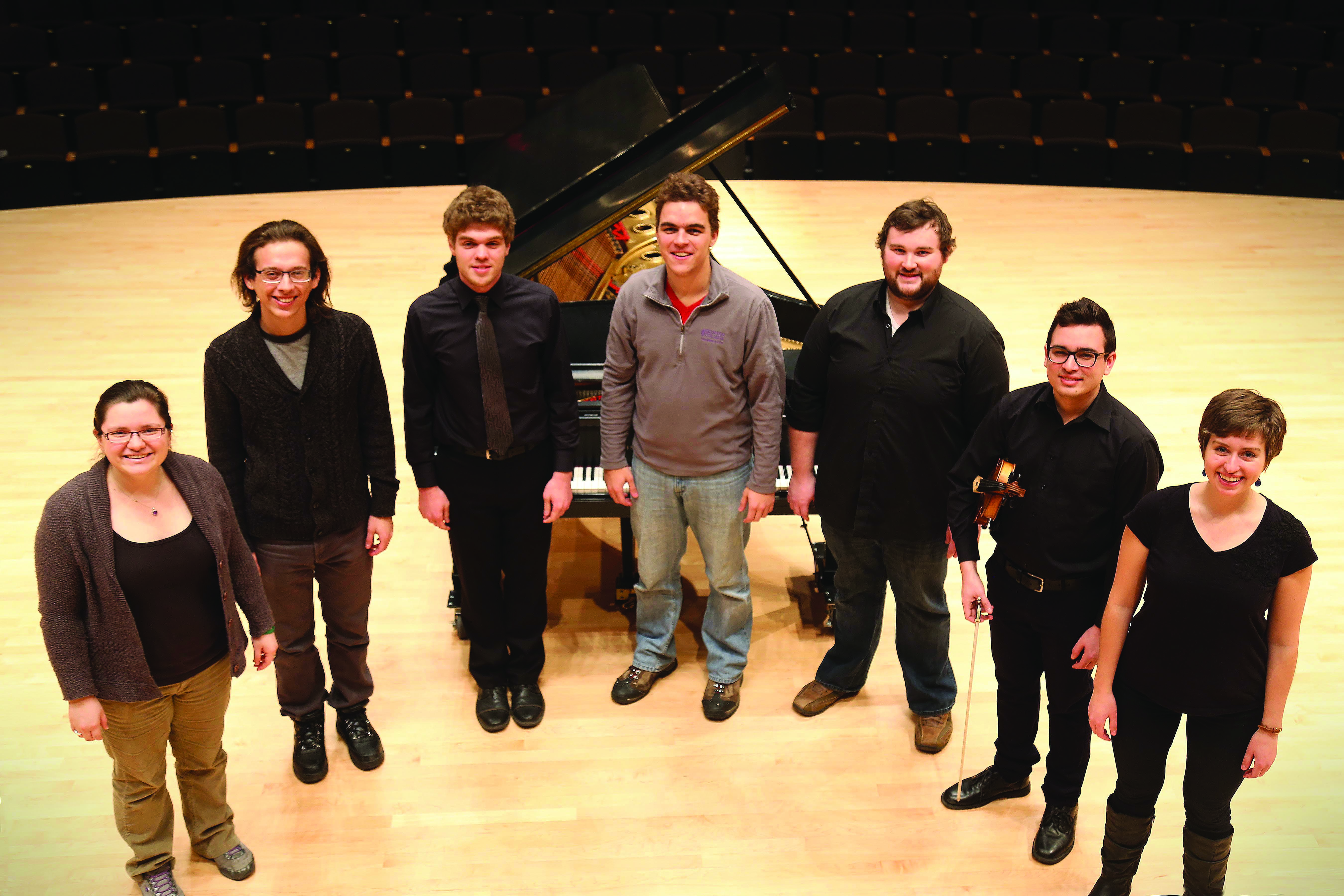 The seven winners of the Concerto-Aria competition pose for a picture in front of a grand piano in Sauder Concert Hall