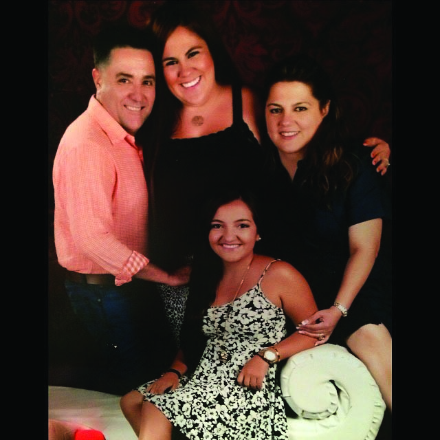 Enrique Fonseca poses for a picture with his wife Elizabeth and his daughters Frances and Ashley