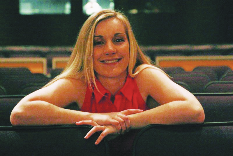 Morgan Yordy leans on seats in an auditorium for a picture