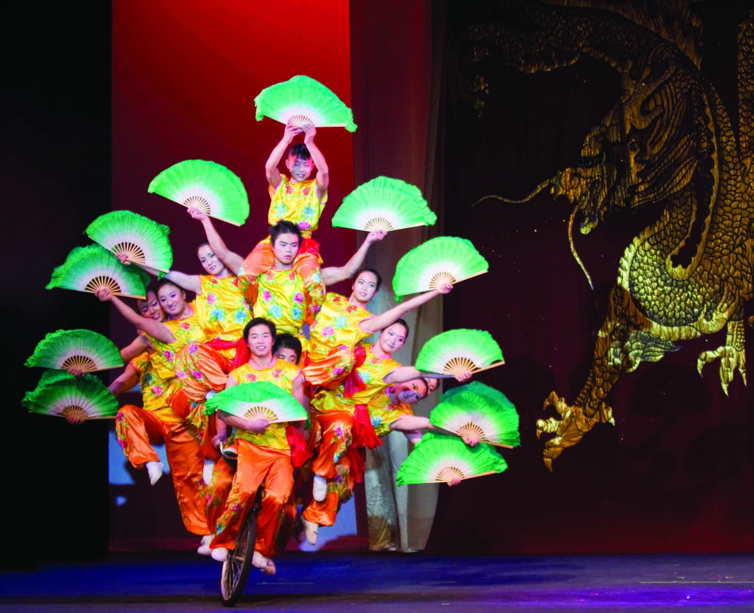 The Peking Acrobats wear bright costumes and hold fans during a performance
