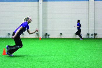 Caption: Kourtney Mueller, junior, conditions with her teammates during softball practice.